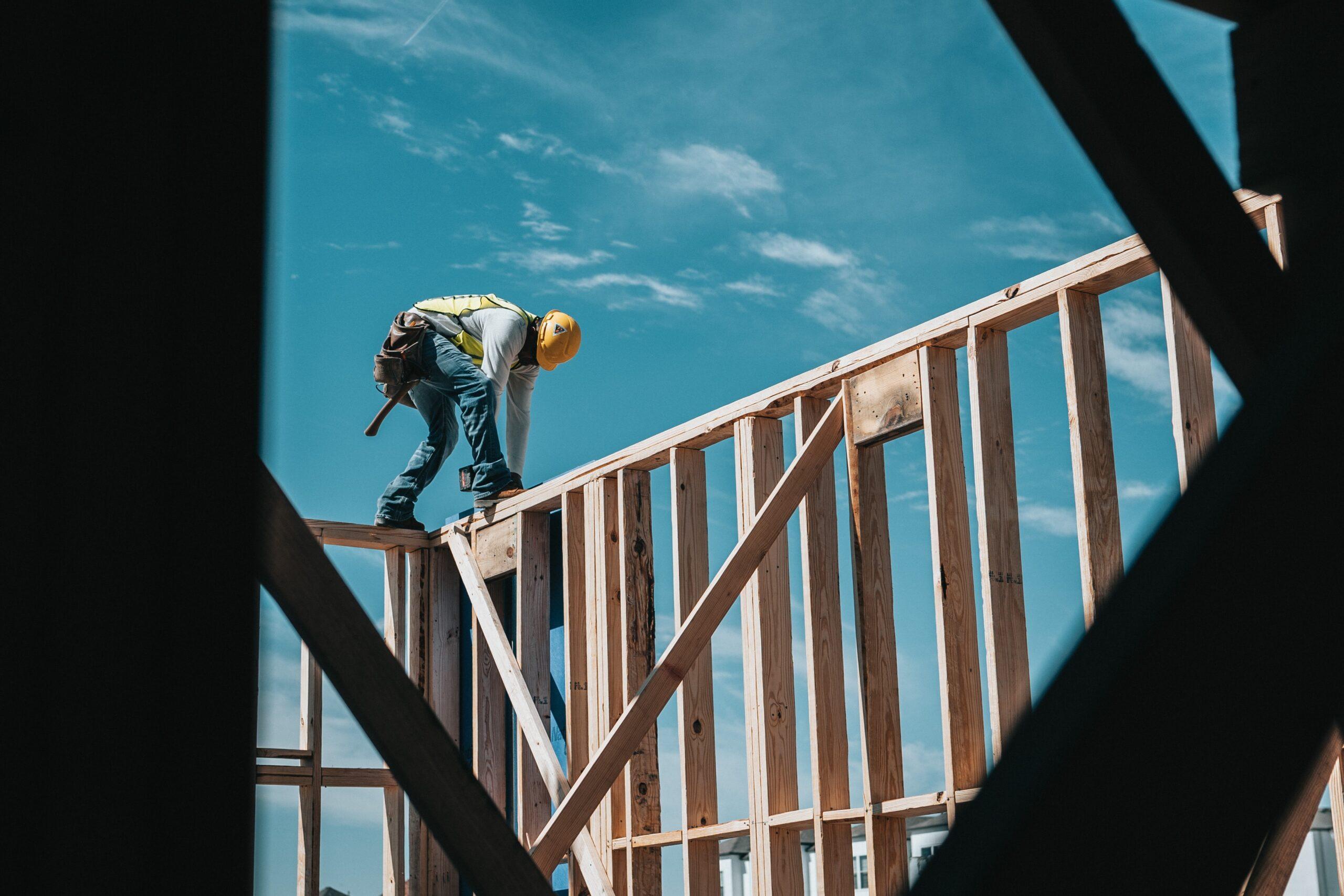 Construction Worker On Wood Building Frame